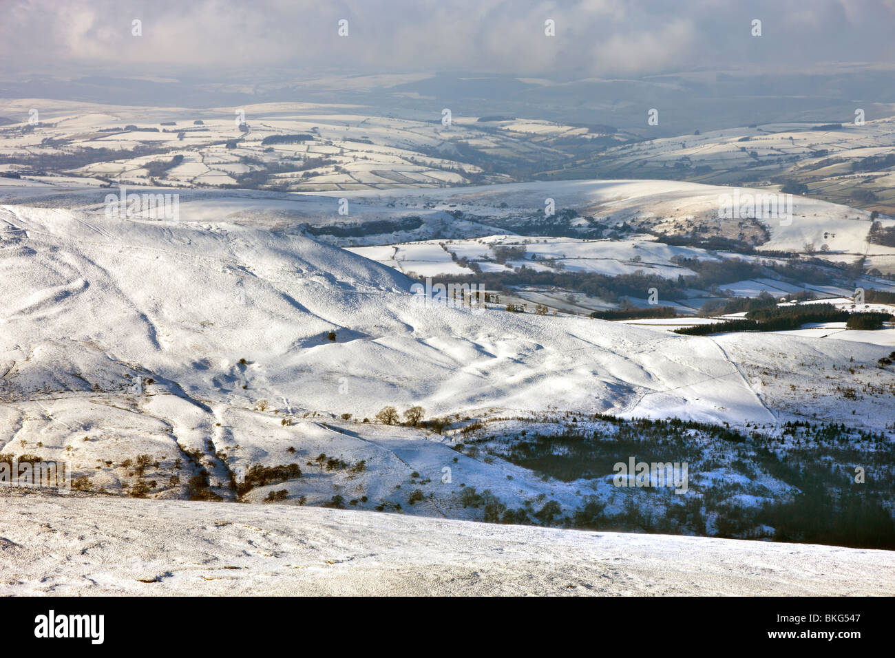 Looking down onto Craig Cerrig Gleisiad and snow covered countryside from the slopes of Corn Du, Brecon Beacons, - Stock Image
