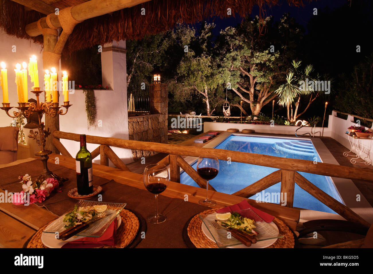 Candles on table set for dinner on balcony of Spanish villa with swimming pool lit at night & Candles on table set for dinner on balcony of Spanish villa with ...