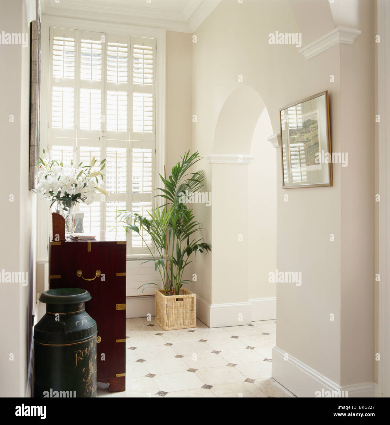 Plantation Shutters On Tall Window In Modern White Hall With