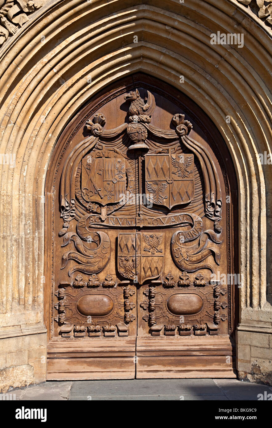 Carved wooden door with heraldic shields Bath abbey England UK - Stock Image