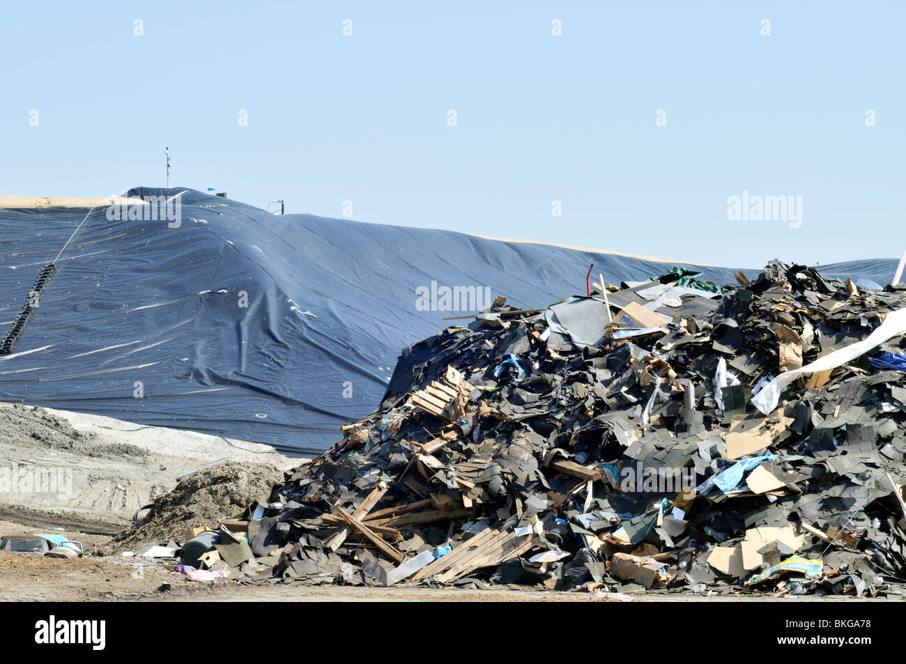 Landfill dump with pile of trash and commercial construction debris with plastic capping  US - Stock Image