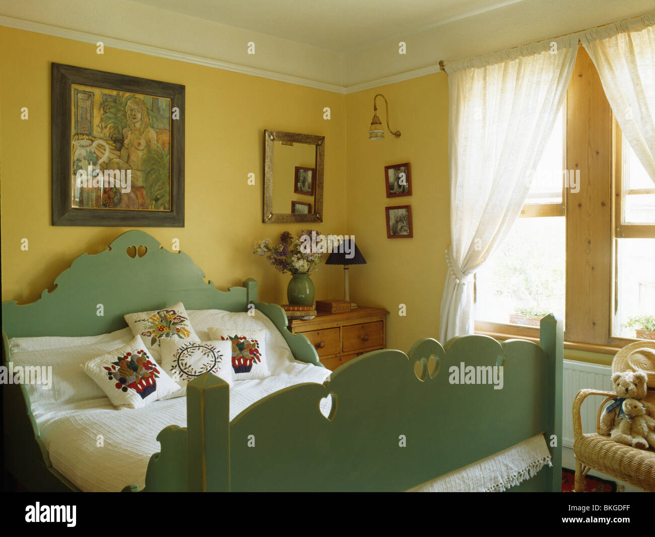 Picture on wall above green painted wooden bed with embroidered ...