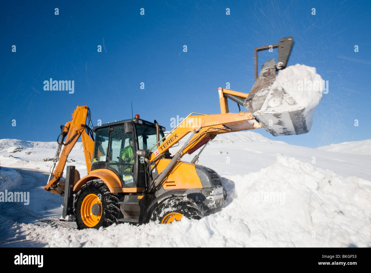 Charlie Middleton, an employee of cumbria vounty council clears snow from the blocked Kirkstone Pass, UK - Stock Image