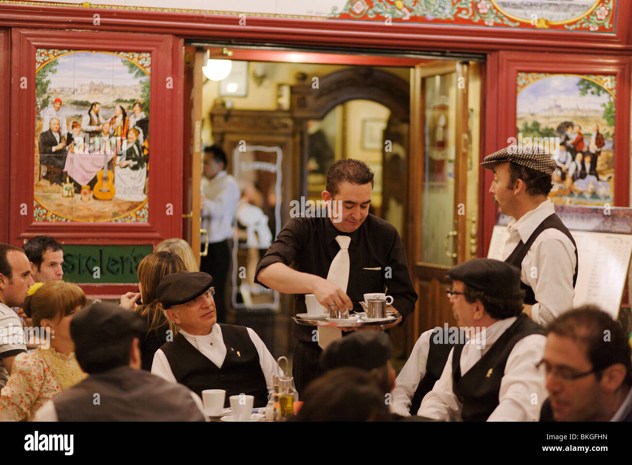 Waiter serving coffee in a pavement cafe, Fiestas de San Isidro Labrador, Madrid, Spain - Stock Image