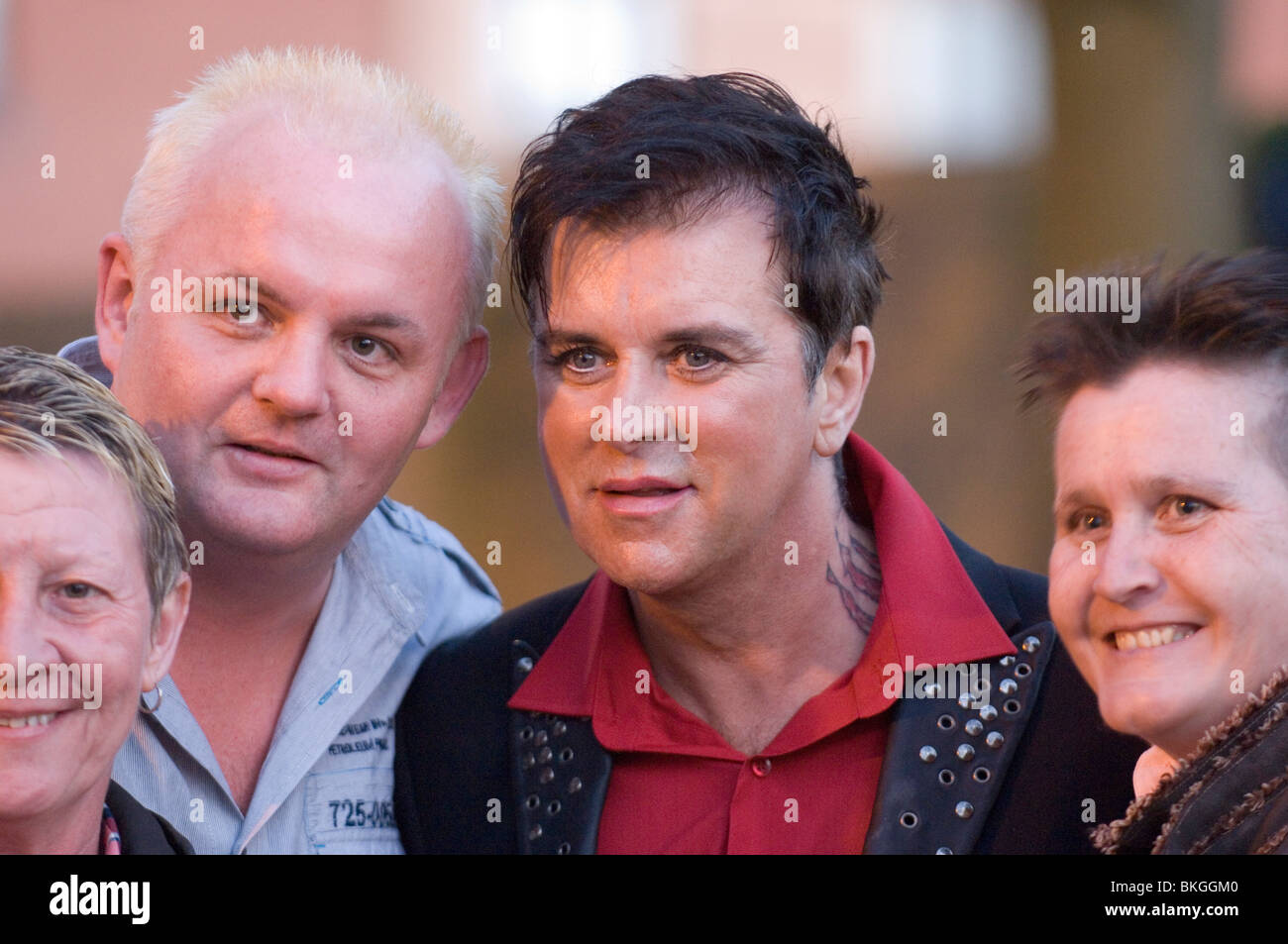 Fans pose for a photo with 80's band Visage lead singer Steve Strange attending the Boy George 'Up Close - Stock Image