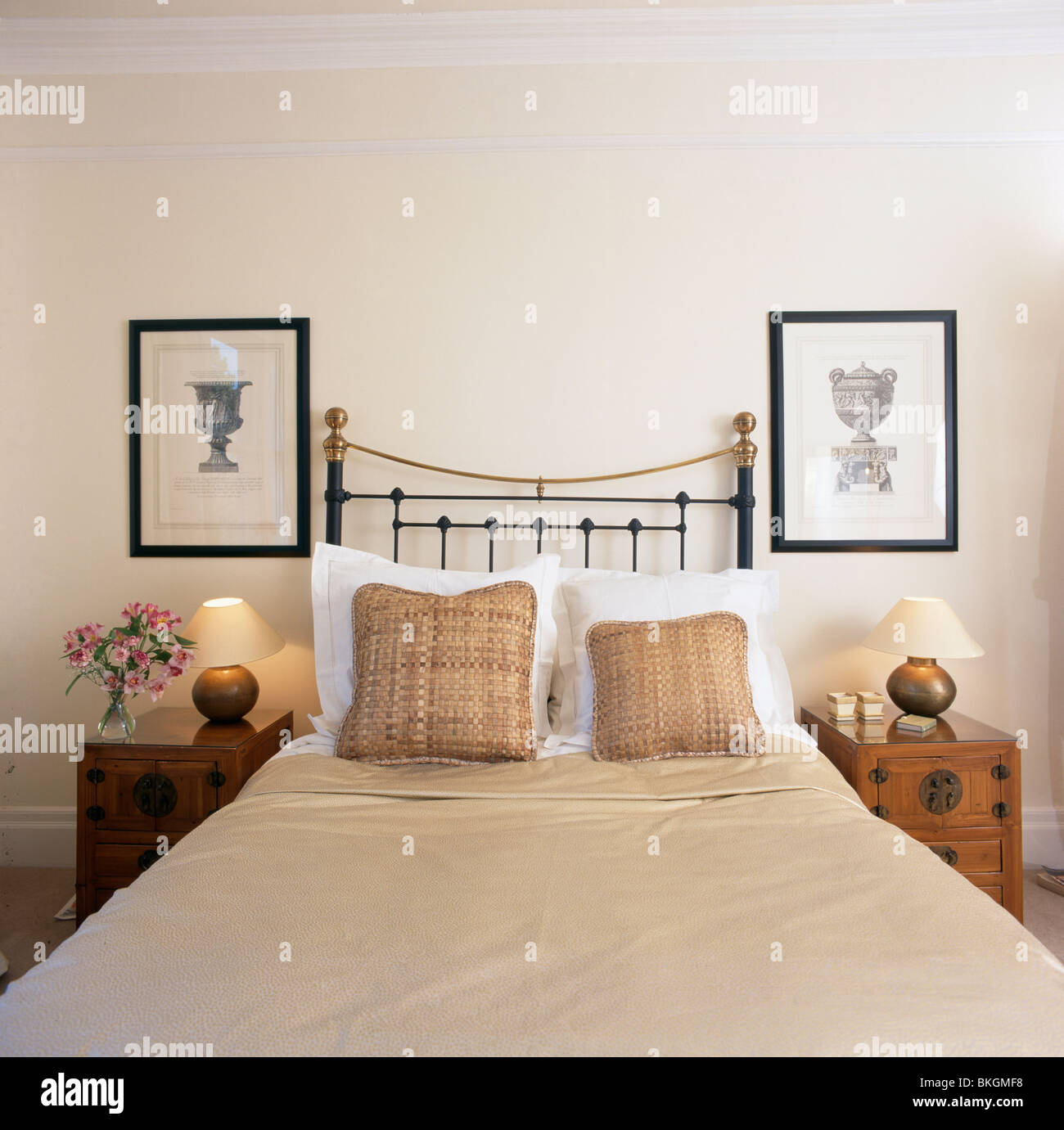 Pictures On Wall Above Brass Bad With Beige Patterned Cushions And Beige  Bed Cover In Townhouse Bedroom With Lighted Lamps