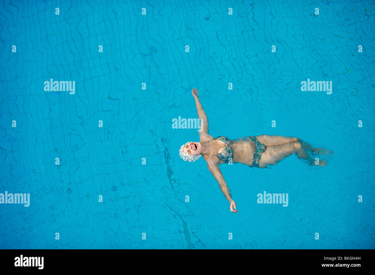 Woman in bikini and hat in a blue swimming pool, lying on back laughing with arms outstretched. - Stock Image