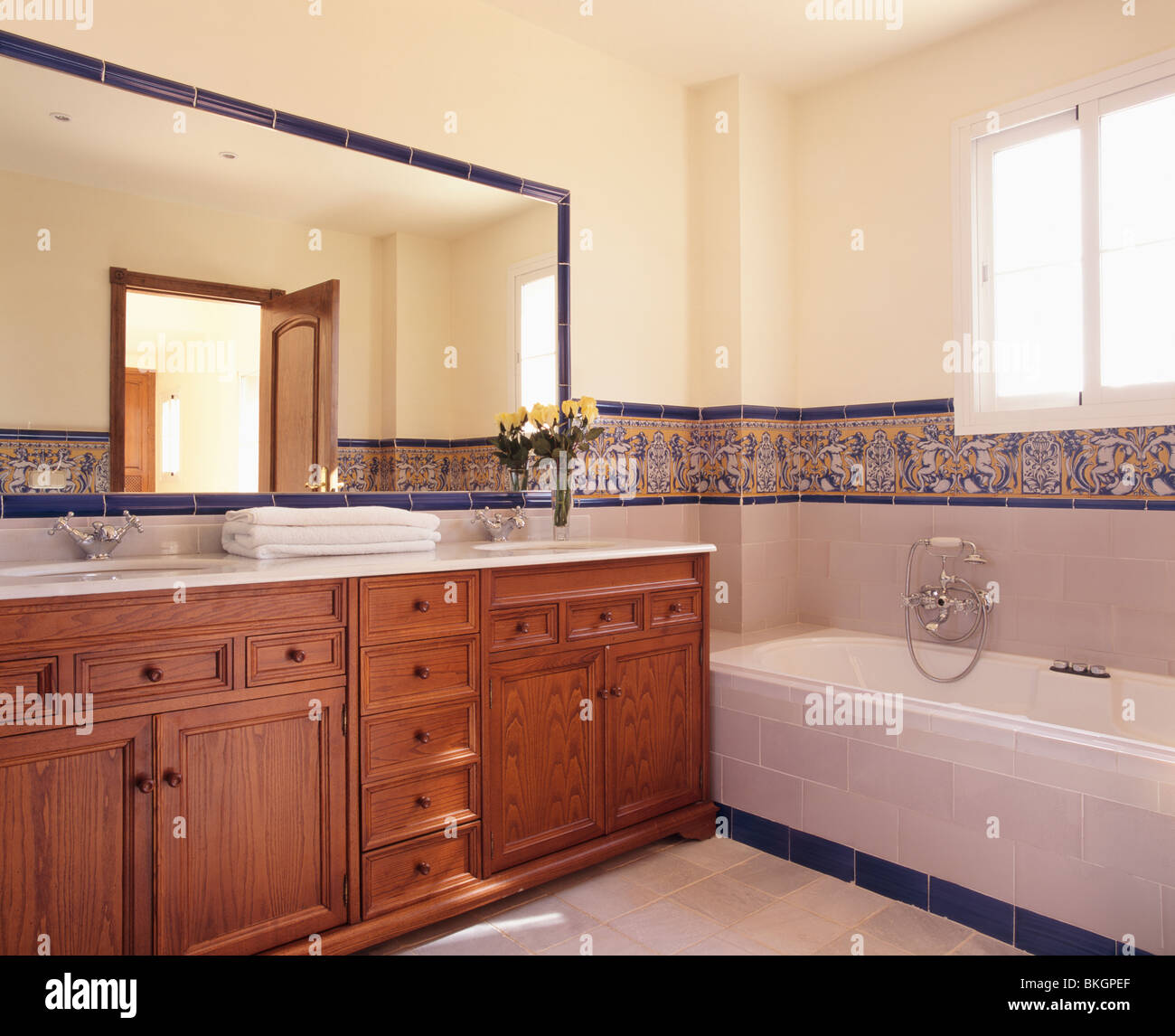 Large Mirror Above Fitted Wood Vanity Unit In Modern Spanish Bathroom Stock Photo Alamy