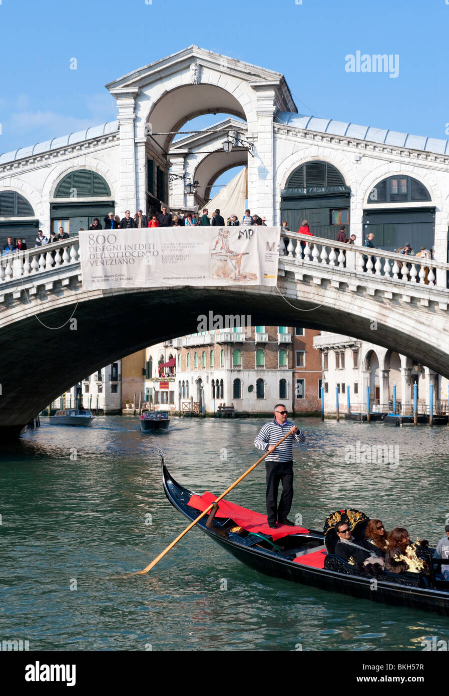 Gondolier and his gondola on the Grand Canal at Rialto Bridge in Venice Italy - Stock Image