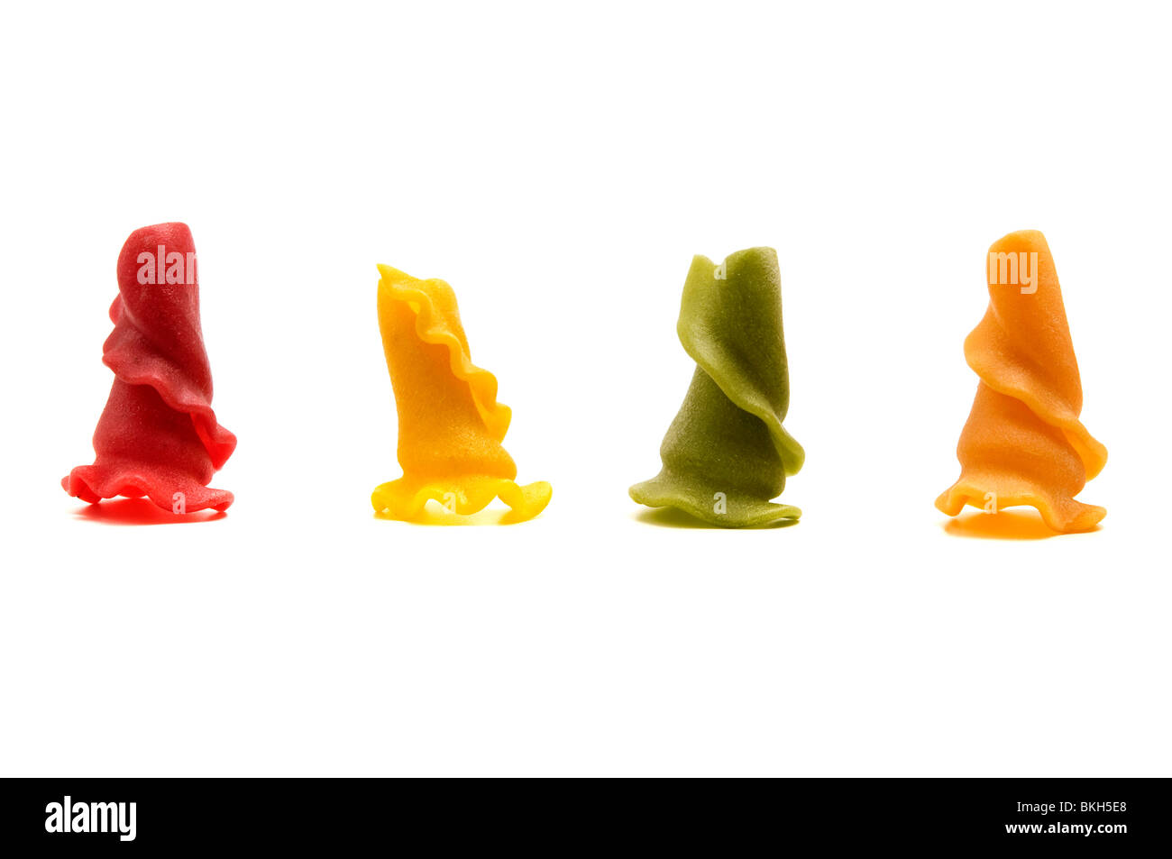 Mixed weird shaped pasta on a white background (Red = Tomato, Yellow = Durum wheat, Green = Spinach, Orange = Turmeric) - Stock Image