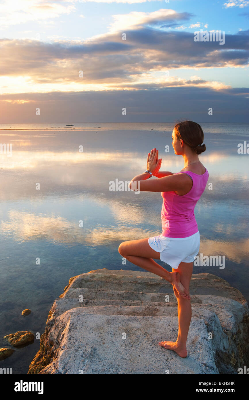 Girl performing yoga pose at end of pier looking into sunset Matabungkay; Batangas; Southern Luzon; Philippines - Stock Image