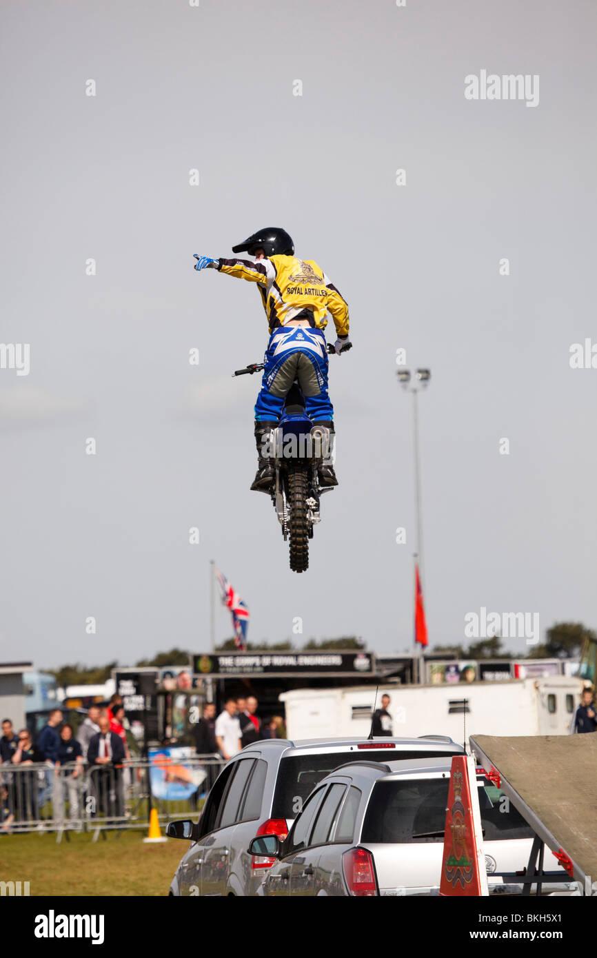 Royal Artillary motorcycle display team member jumping over cars at an Army show. - Stock Image