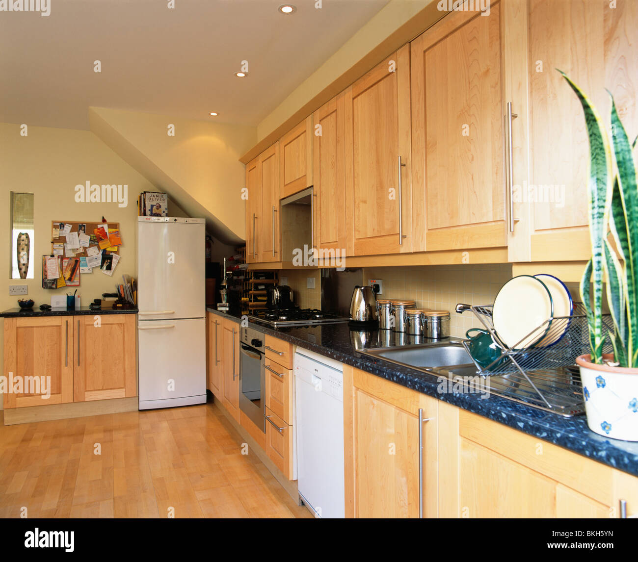 Pale Wood Fitted Units With Granite Worktops In Modern Kitchen With