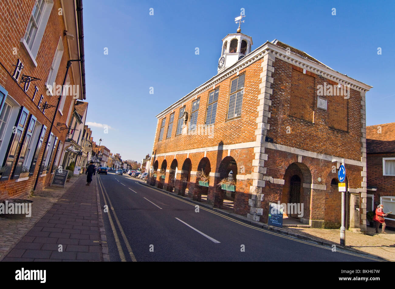 Horizontal wide angle view of the prominent red brick Market Hall in Old Amersham High Street on a sunny day. Stock Photo