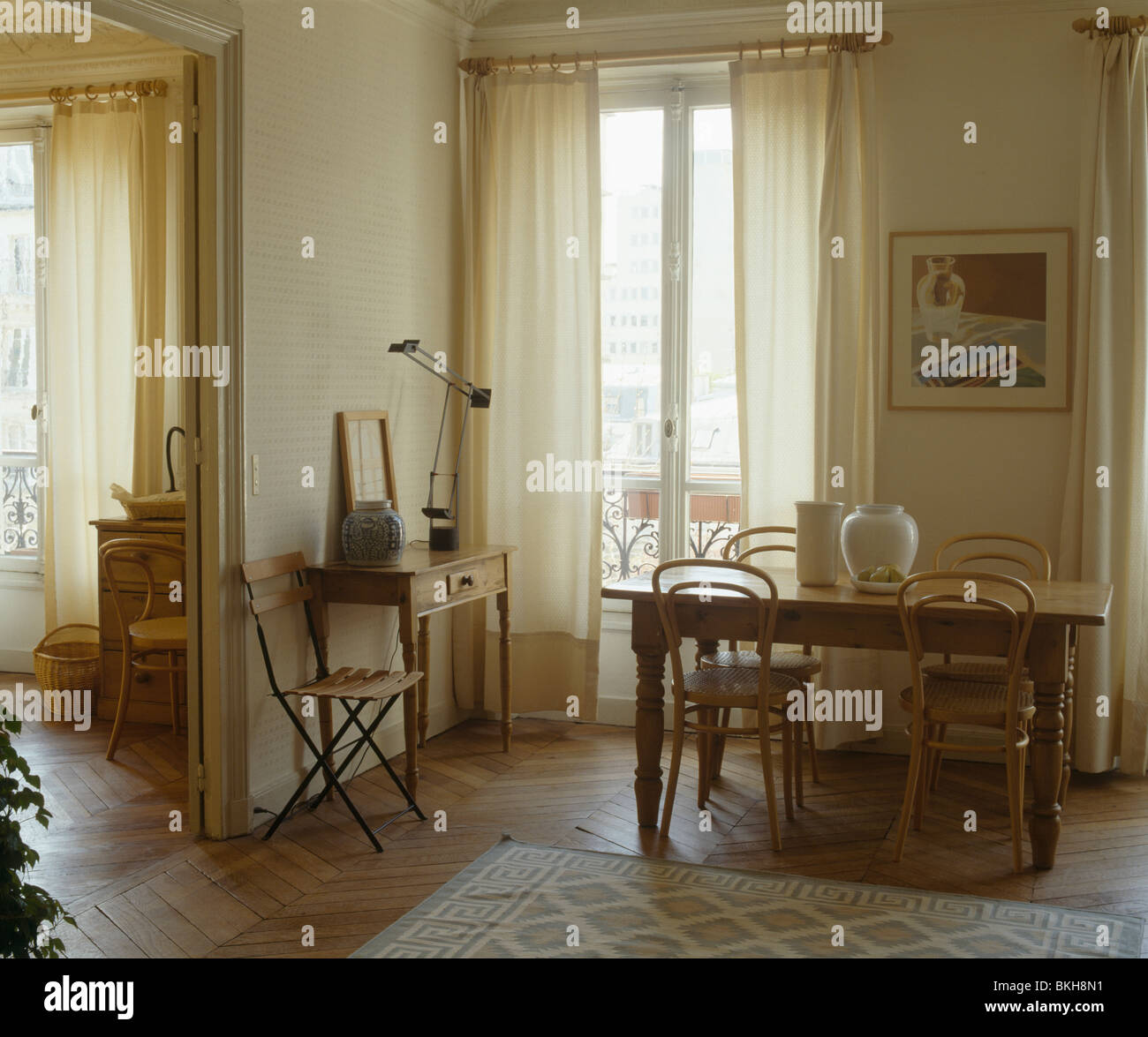 Antique Bentwood chairs and old pine table in cream apartment dining room  with cream curtains at French windows - Antique Bentwood Chairs And Old Pine Table In Cream Apartment Dining