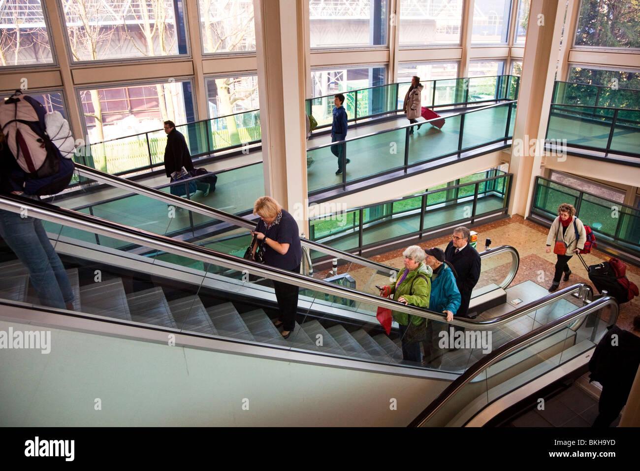 People on ramp and escalator at Gatwick airport England UK - Stock Image