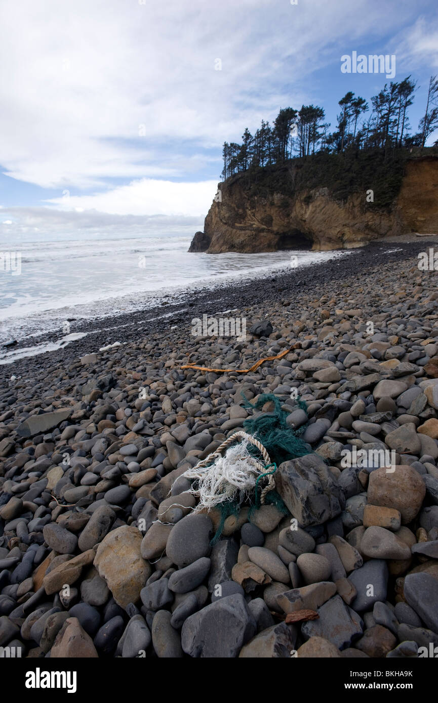Pieces of fishing net littering the beach. - Stock Image
