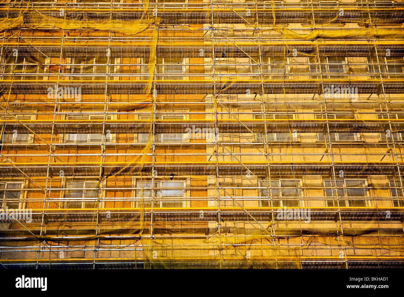 Buildings undergoing restoration covered in scaffolding and mesh fabric, Madrid, Spain - Stock Image