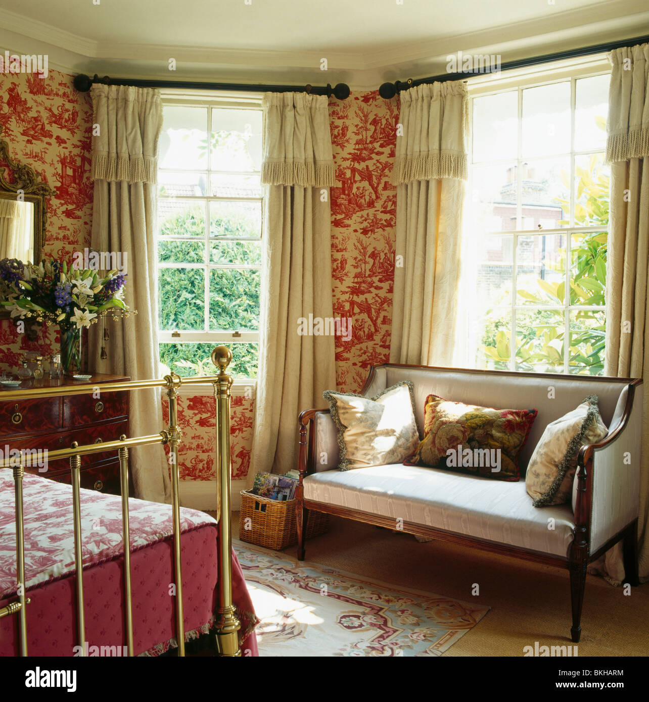 Elegant Red Toile De Jouy Wallpaper In Bedroom With Antique Sofa In Front Of Window  With Cream Curtains