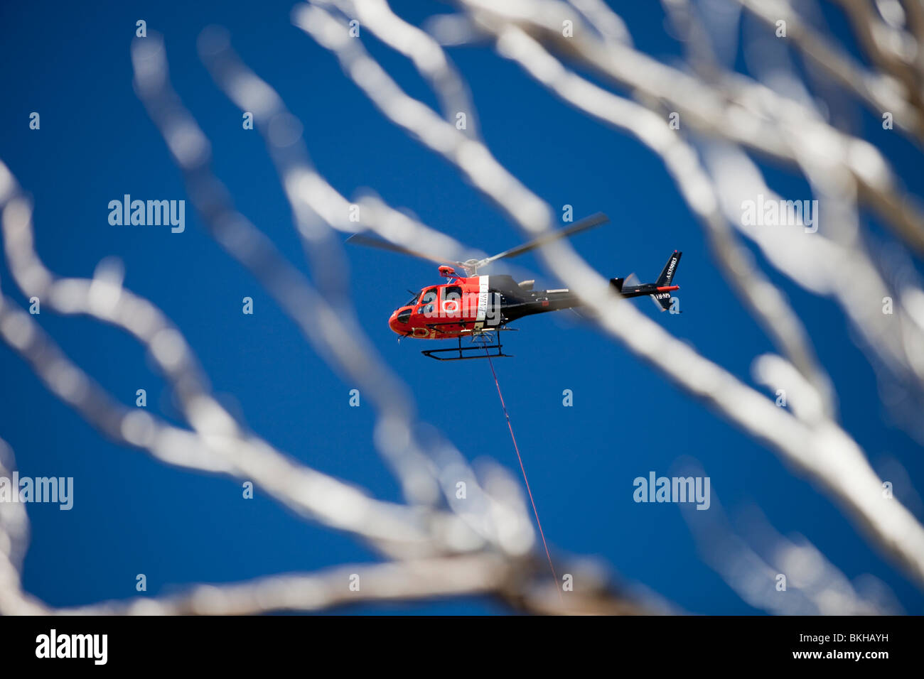 National Park staff using a helicopter to move goods in the Snowy mountains, Australia. - Stock Image