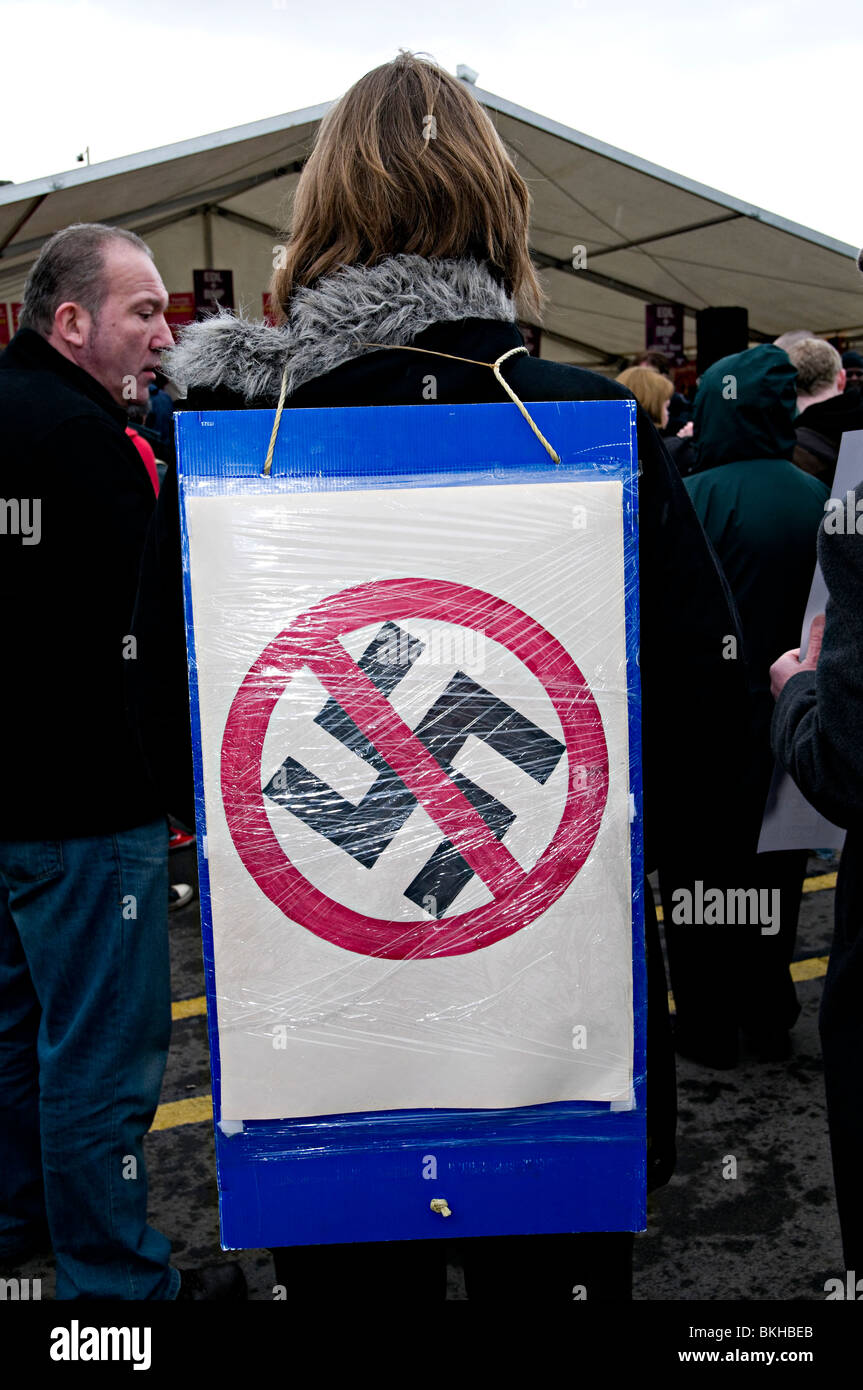 a girl standing with an anti nazi sign with a swastika crossed out at an anti edl rally dudley - Stock Image
