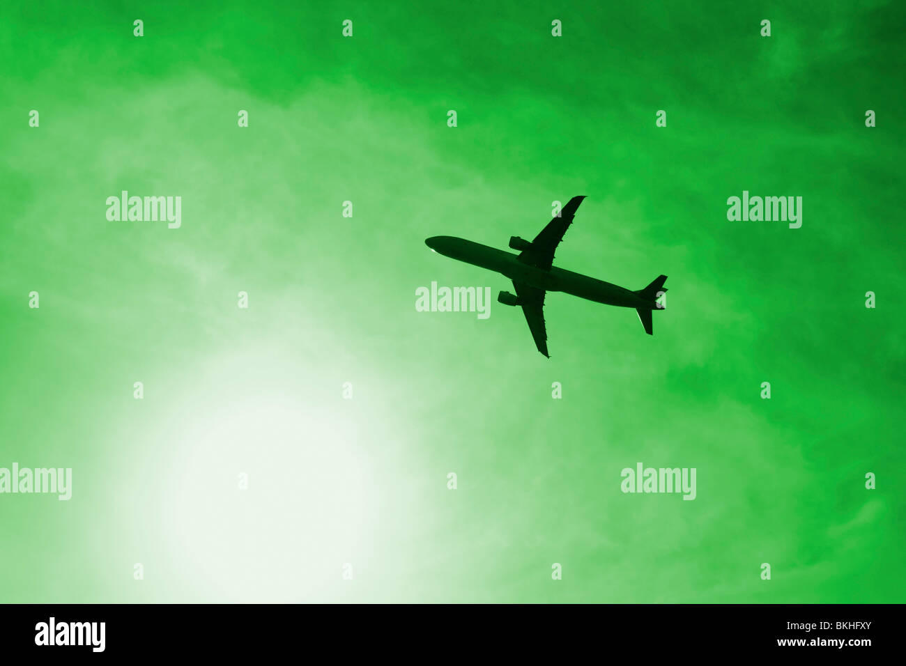 Plane near sun against green sky. Could be used to depict pollution, air travel, carbon footprint... - Stock Image