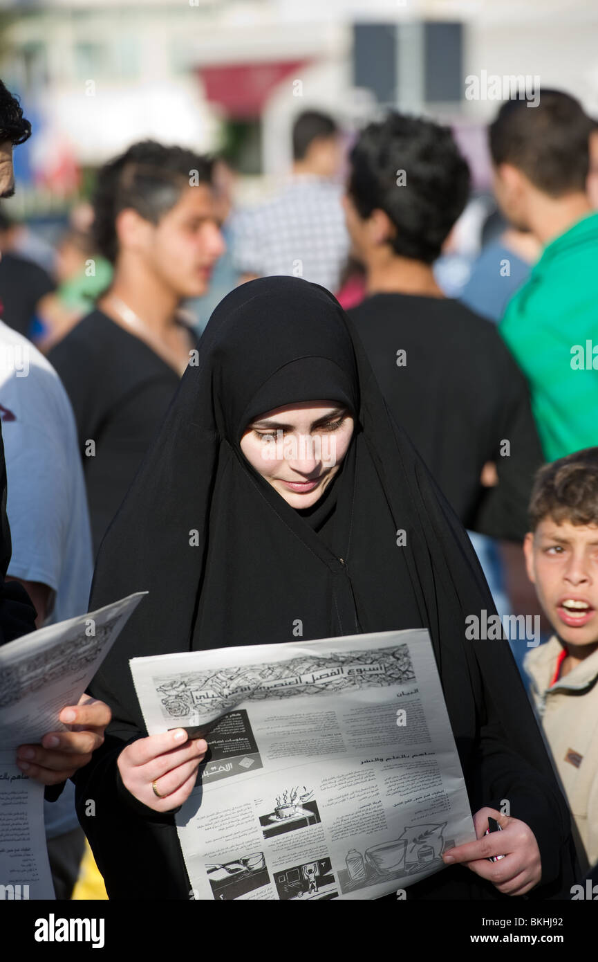 Shiite woman reading the newspaper - Stock Image
