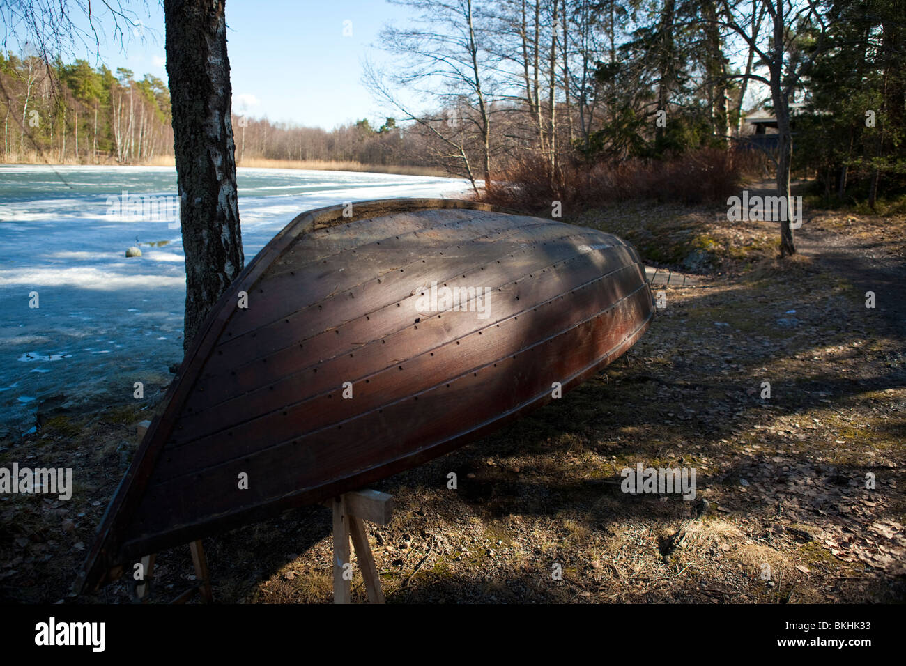 Wooden boat on the Stockholm archipelago with frozen lake background - Stock Image