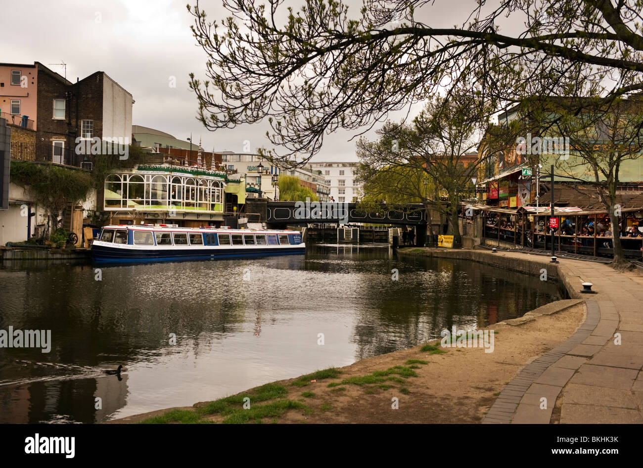 A  view of Regents canal and towpath a London waterway towards a footbridge over Camden Lock. - Stock Image