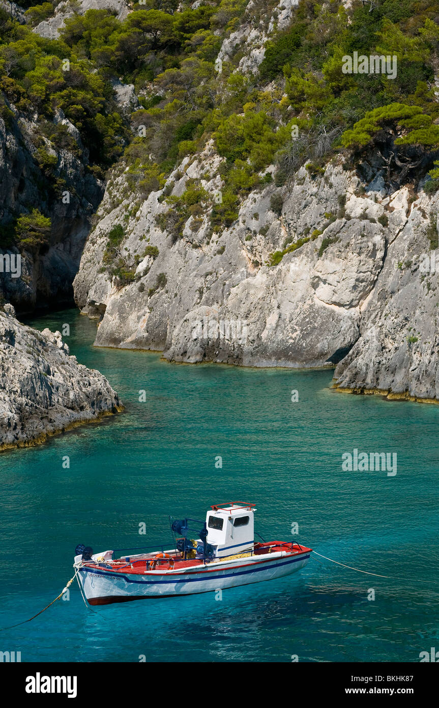 Small rocky bay with crystal clear waters and touristic boat in Zakynthos, Greece - Stock Image
