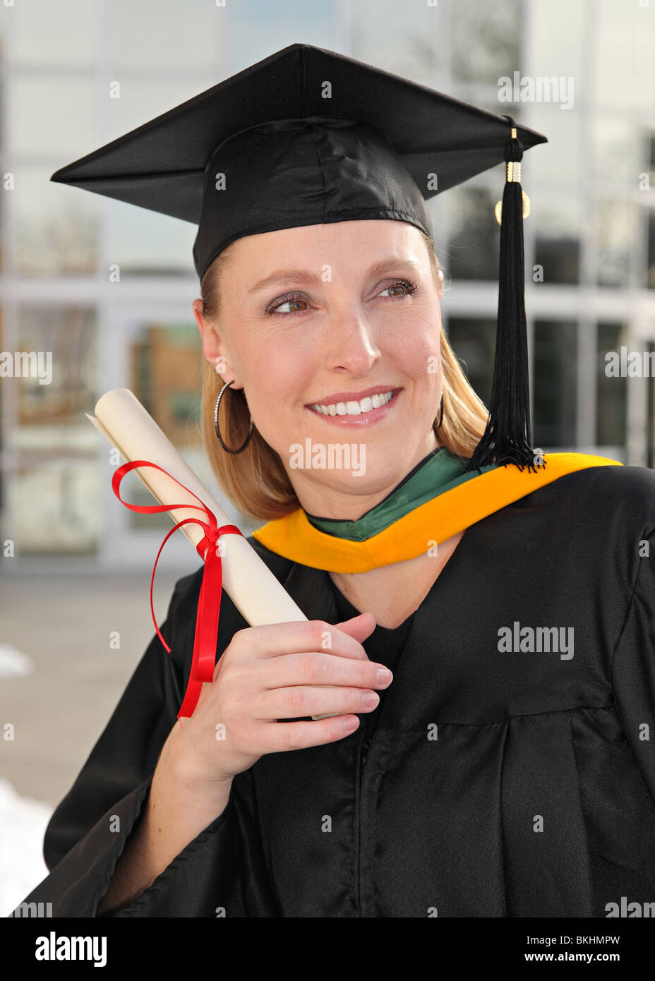 attractive blond woman in graduation uniform holding a diploma at the university - Stock Image