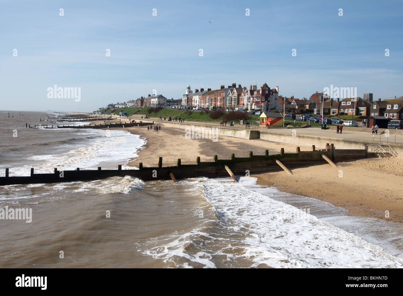Shot from Southwold Pier showing breakwaters and beach with houses and hotels in background with the lighthouse - Stock Image
