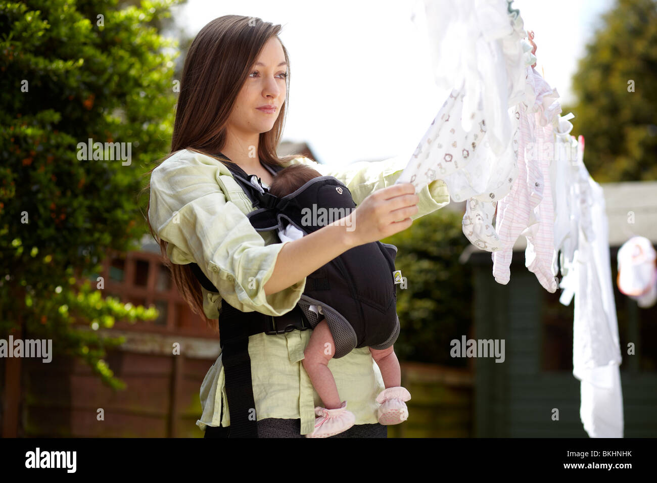 Woman with baby taking in washing from line - Stock Image
