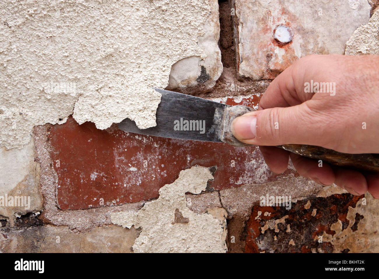 House Maintenance Man Scraping Off Flaking Paint On Old Brickwork In Stock Photo Alamy