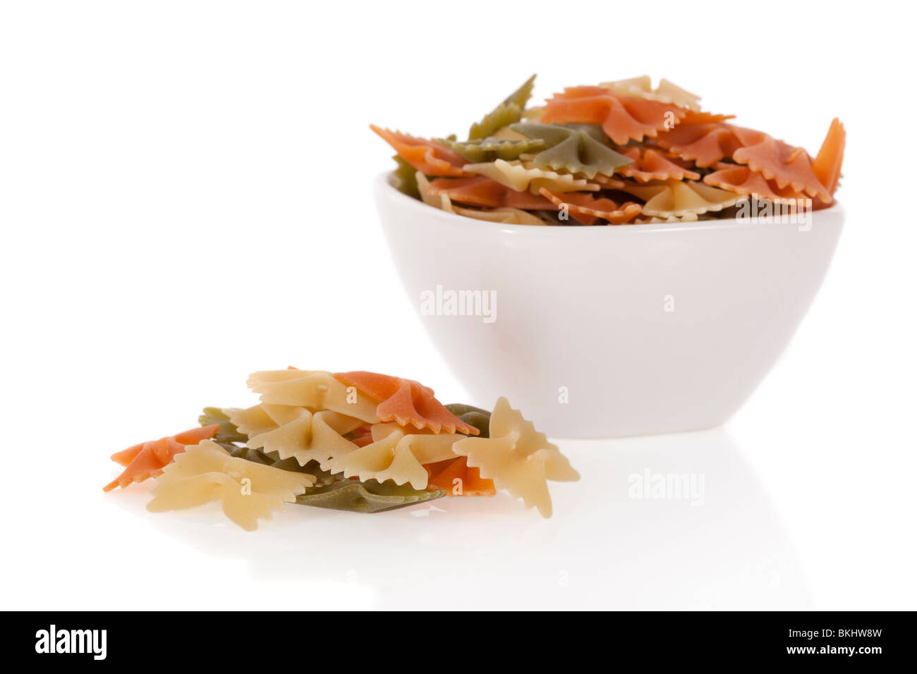 Tricolore farfalle pasta in a bowl isolated on a white background - Stock Image