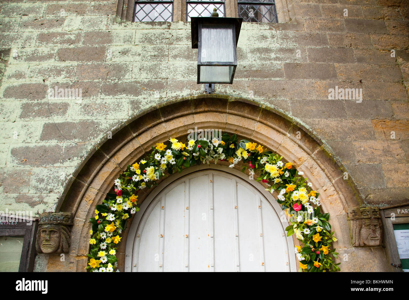 Porch lighy and flowers surronding the entrance to Tillington Church with it's Scots Crown Spire Stock Photo
