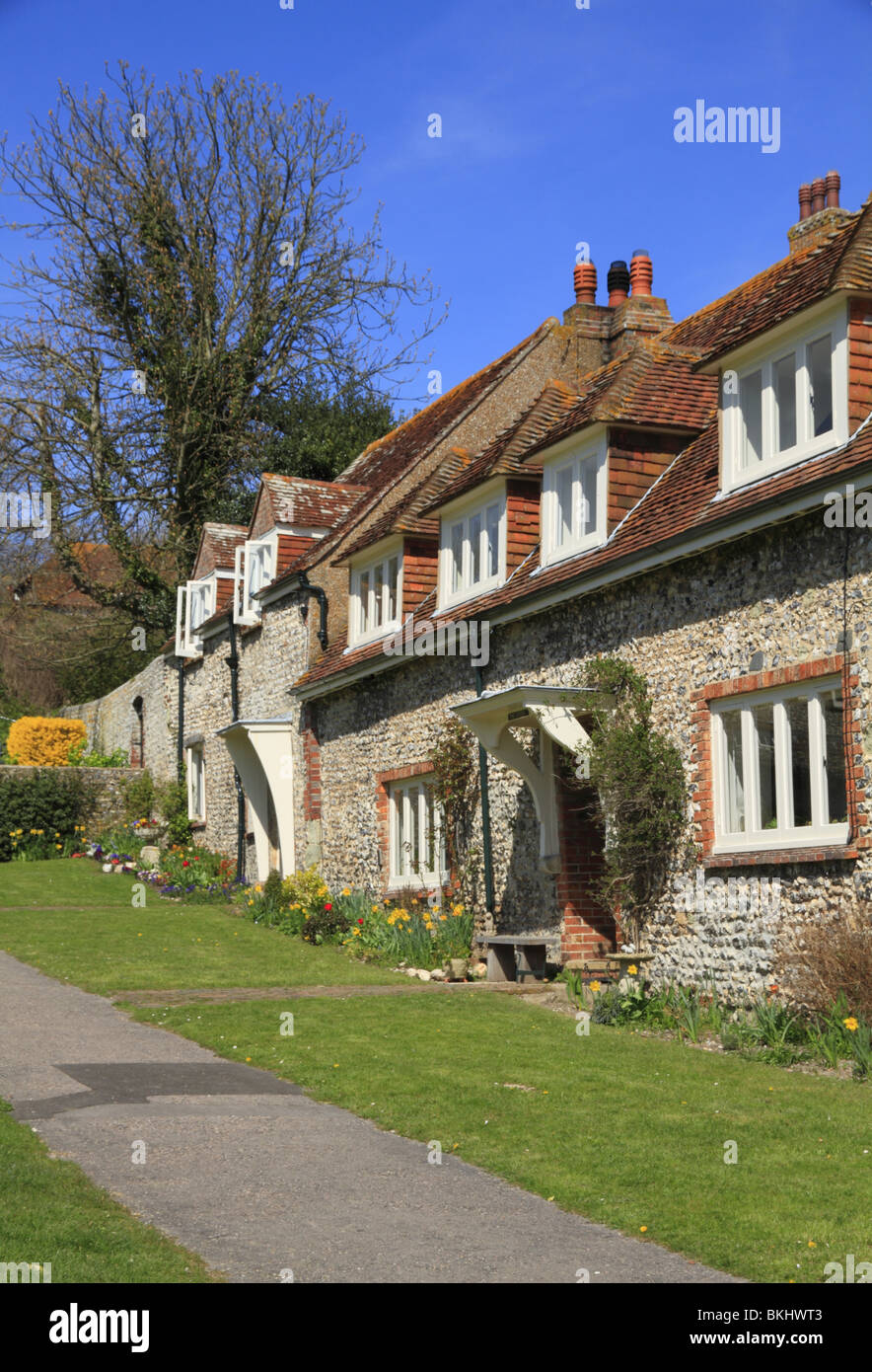 A terrace of traditional flint cottages, fronting onto the village green at East Dean, East Sussex - Stock Image