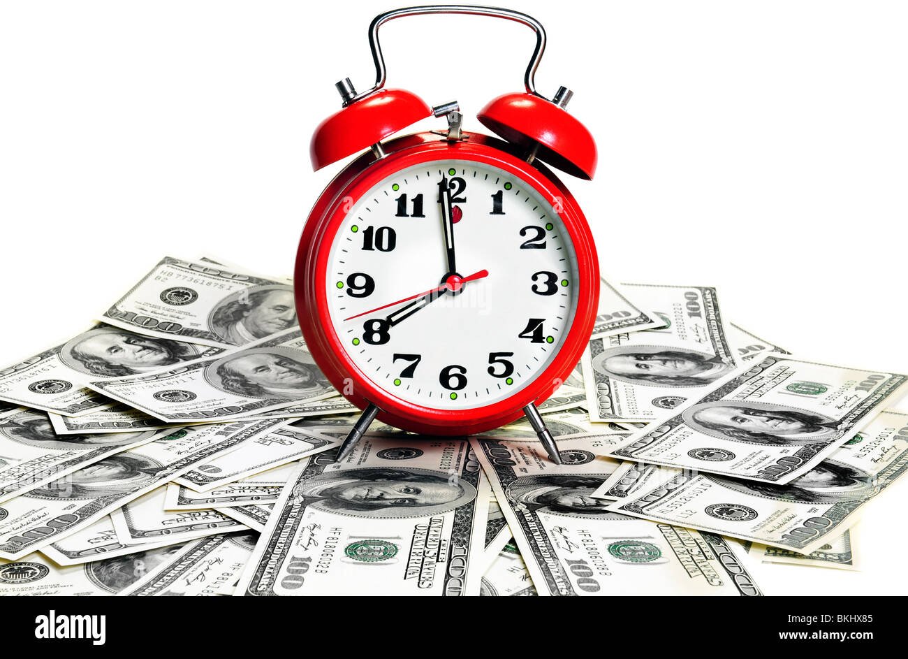 'Time is money' concept - classic alarm clock over dollars. High contrast - Stock Image