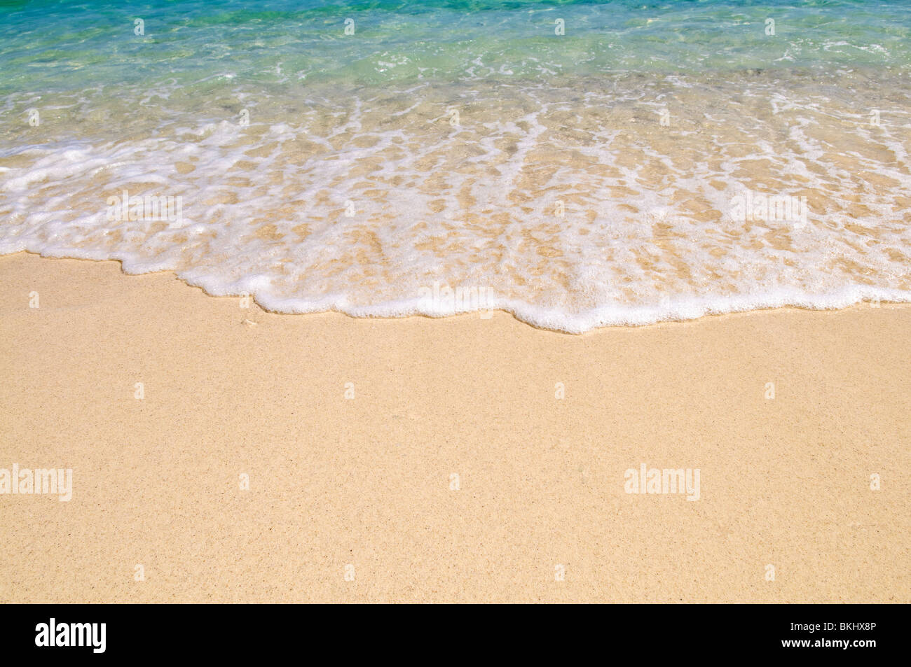 A wave breaking on the sand - Stock Image