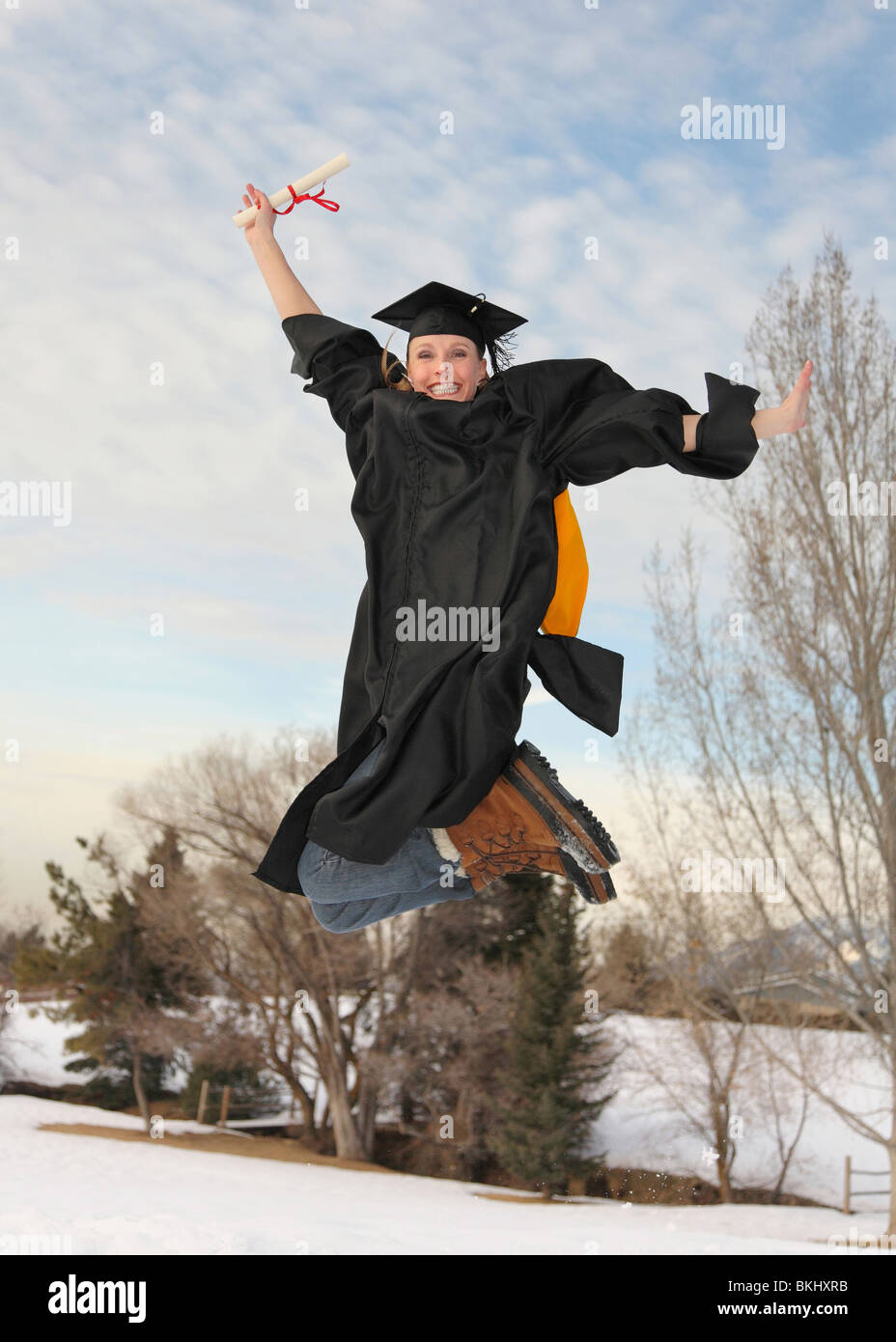 ff34e8e6777 excited blond woman in graduation outfit and diploma outdoors in winter  jumping high in the air