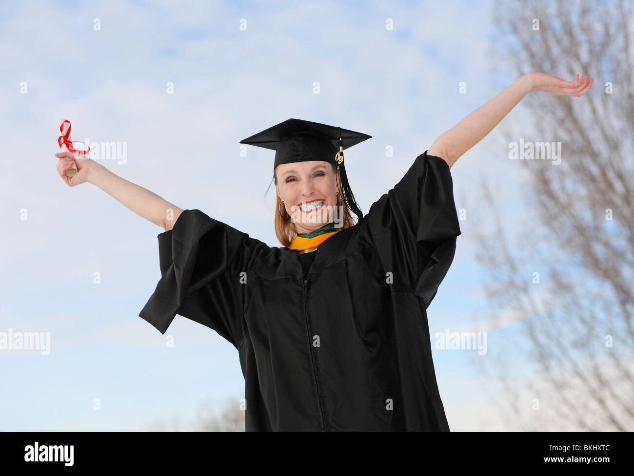 excited attractive graduate with diploma celebrating with arms stretched in the air Stock Photo