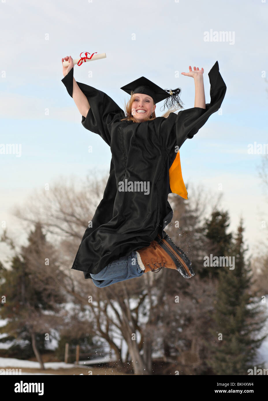 excited blond woman in graduation outfit and diploma outdoors in winter jumping high in the air - Stock Image