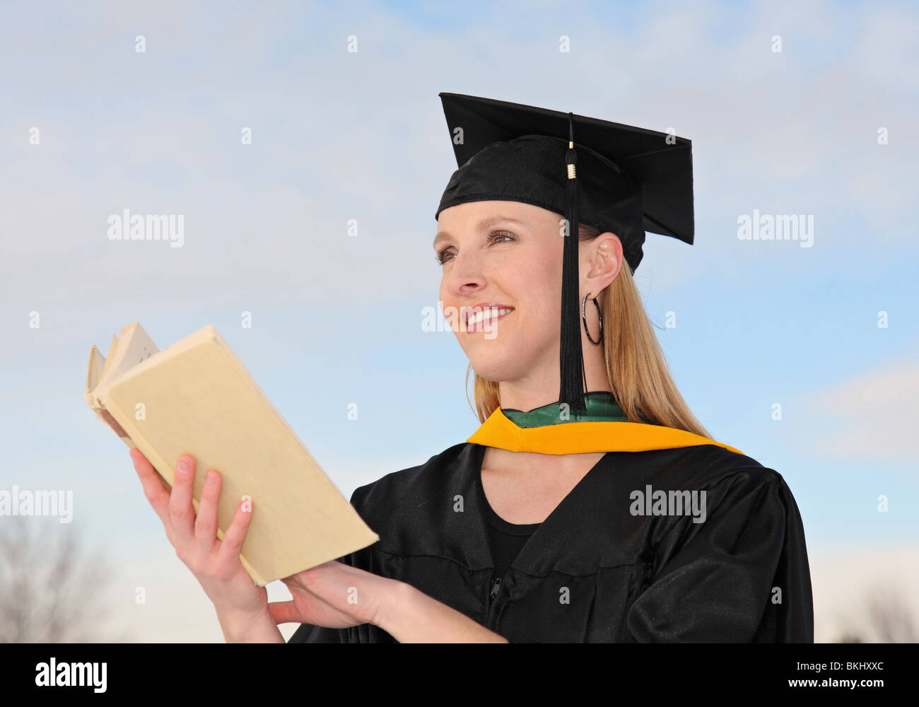 attractive female graduate holding text book outdoors - Stock Image