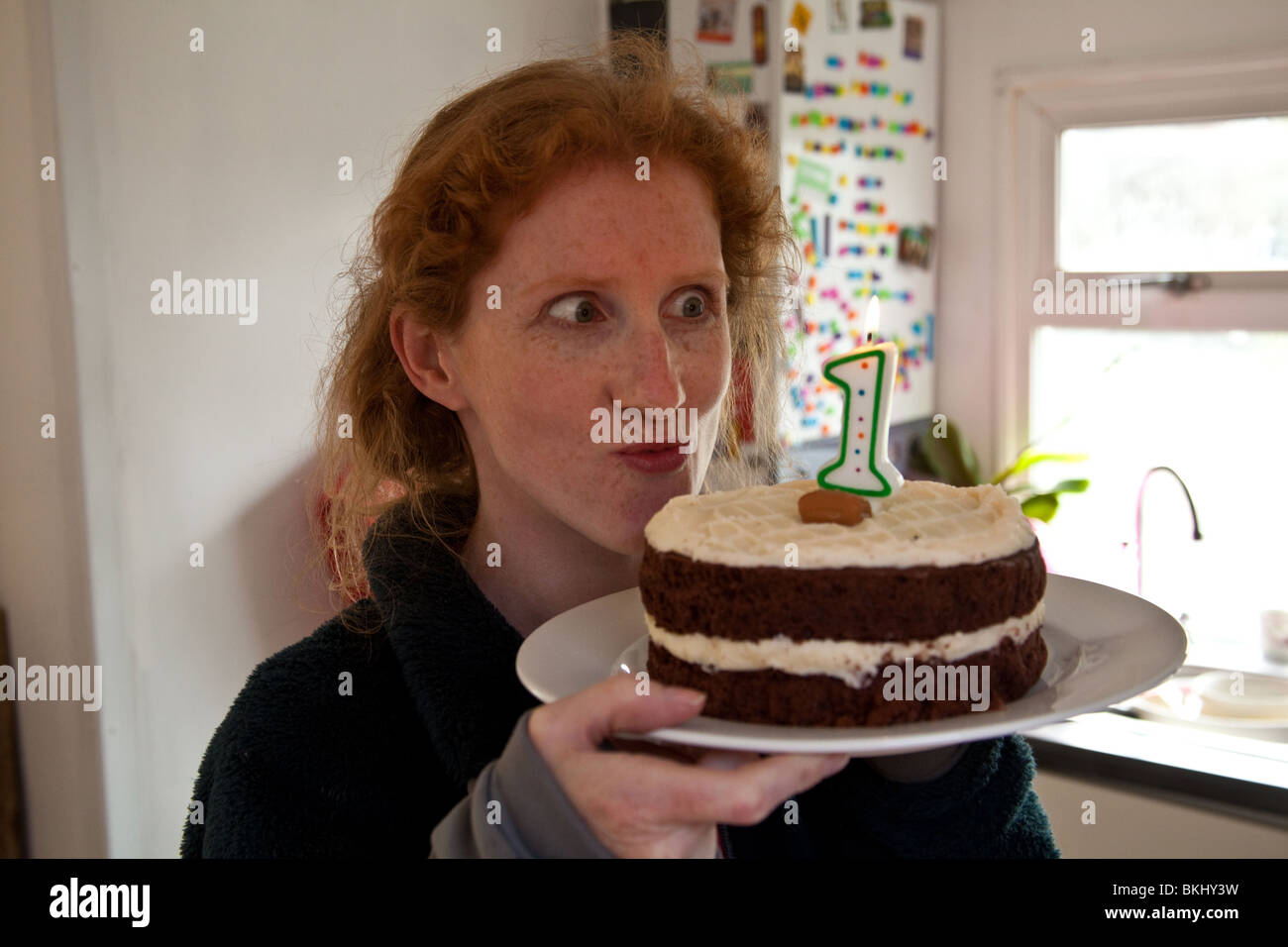Redheaded woman looking at a chocolate, birthday cake with a number 1 candle. - Stock Image