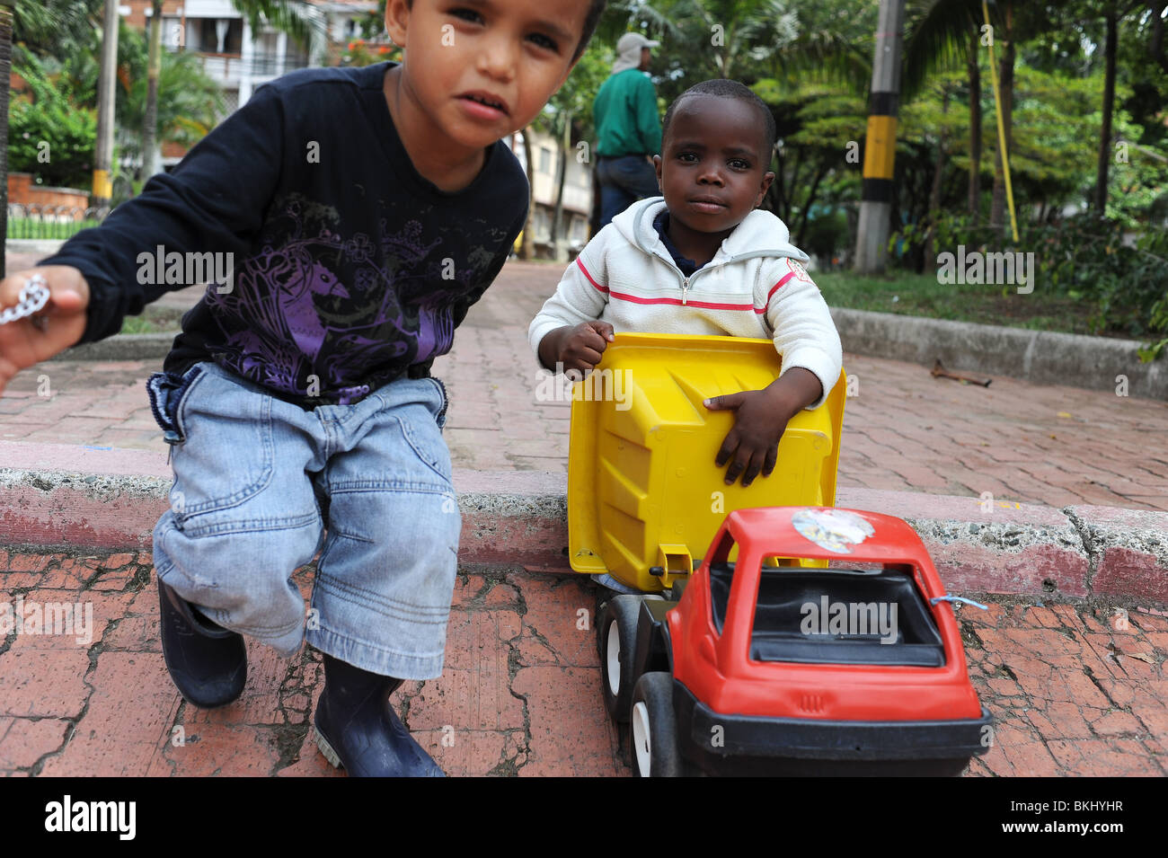 Two boys 3 and 4 years playing with truck in park in Medellin. - Stock Image