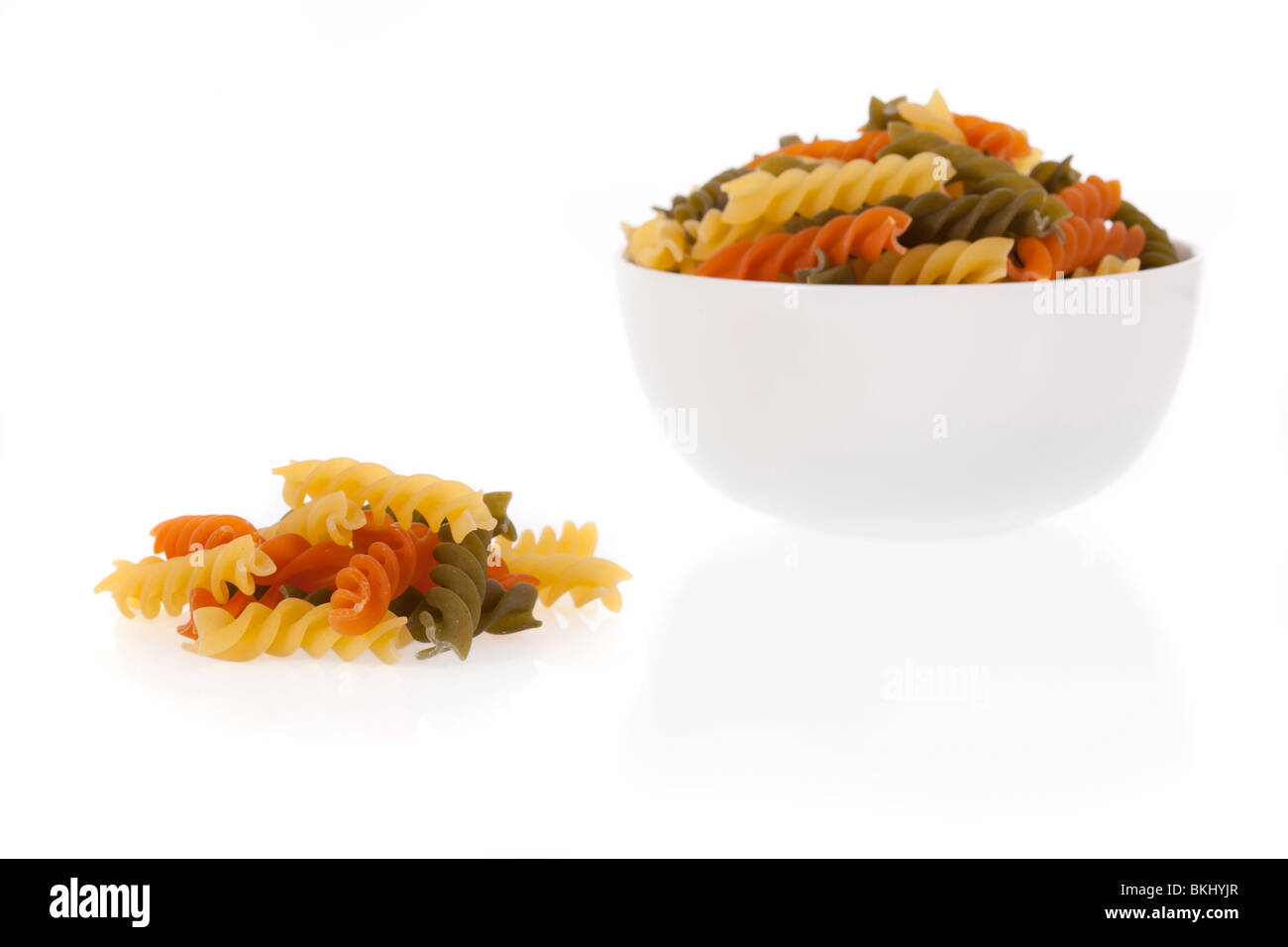 Tricolore fusilli pasta in a bowl isolated on a white background - Stock Image