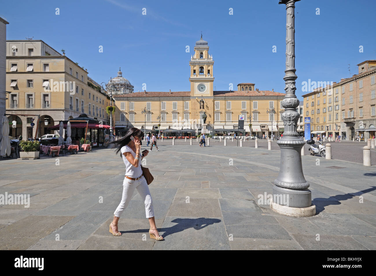 Smart young woman using moblie phone in Piazza Garibaldi public square with the 1760 Palazzo del Governatore and Stock Photo