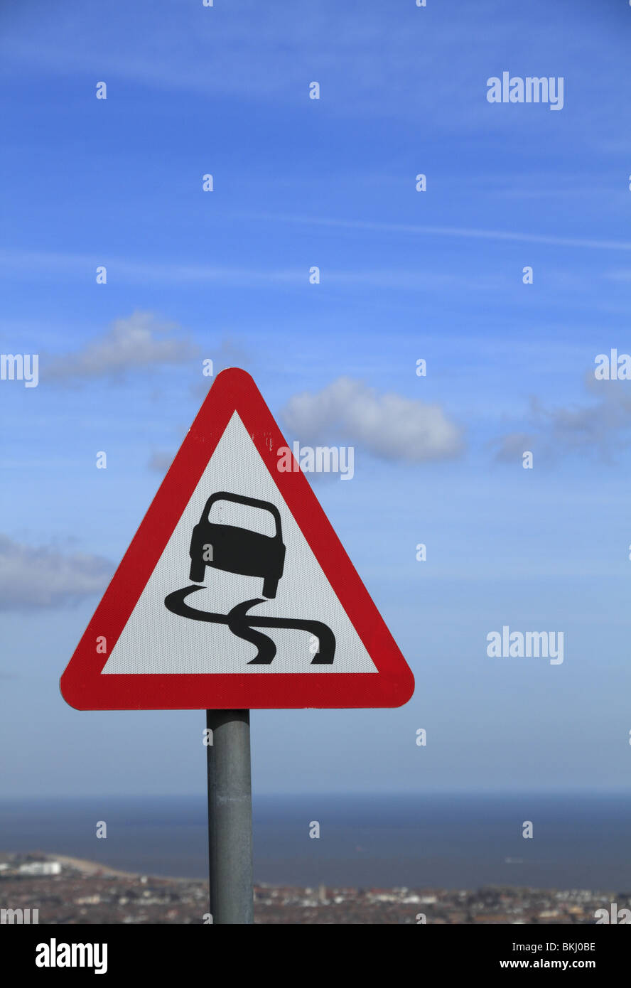 A road sign warns motorists of the potentially slippery surface near Eastbourne, East Sussex - Stock Image