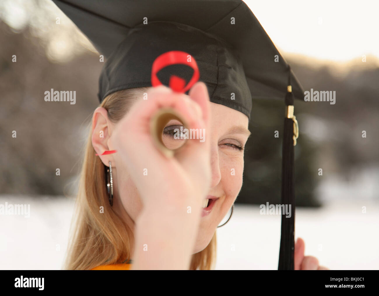 happy girl in graduation cap looking through rolled up diploma - Stock Image