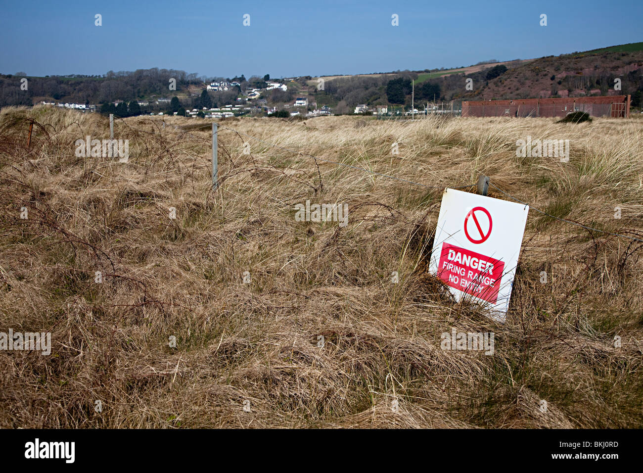 MOD danger firing range no entry sign on barbed wire Pendine Wales UK - Stock Image